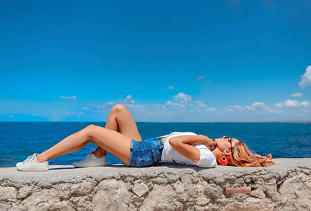 Side view of young blonde in denim shorts and white t shirt lying sensually on stone fence against blue sea in summer day