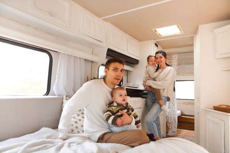 Portrait of the smiling happy family with kids in the house on wheels indoor