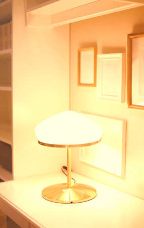 Cozy table corner with blank photo frames on wall and burning lamp at home 版權商用圖片