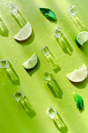 Fresh mint leaf and ice cubes with droplets and lime on green background. Summer background 版權商用圖片