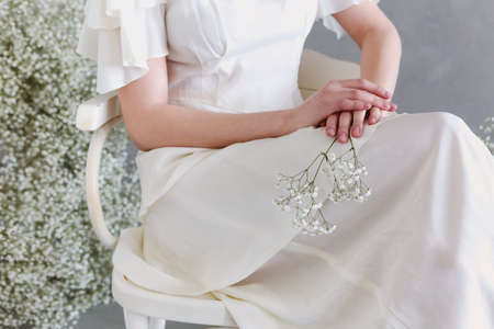 Faceless elegant woman in old fashioned white dress sitting on chair and holding twig of baby breath flower
