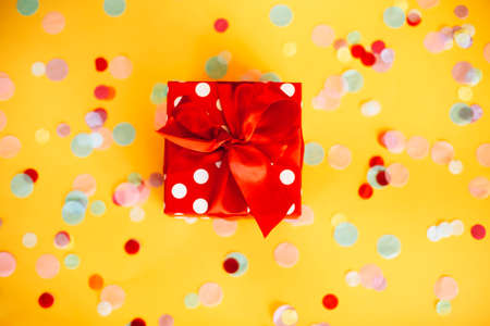 Top view of red polka dot gift box with ribbon placed on yellow surface sprinkled with colorful confetti