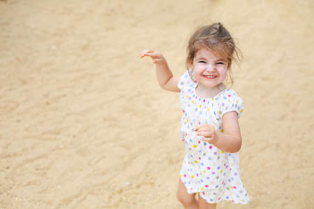 Cute blond baby girl with sun cream on her face in beautiful dress walking on a long sandy beach