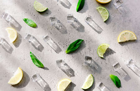 Fresh mint leaf and ice cubes with droplets and lime on cement background. Summer background 版權商用圖片