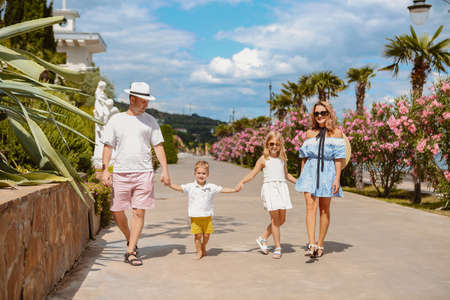 Adult man and woman with little boy and girl all holding hands and enjoying summer vacation walking on promenade in flowers