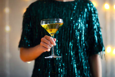 Crop female in shiny dark green party dress holding glass with champagne while standing against blurred background with light garlands 版權商用圖片