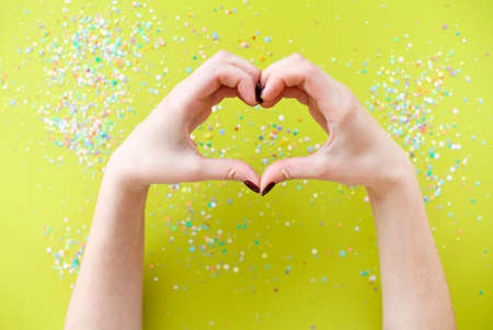 Top view of crop anonymous female with bright manicure showing heart gesture with fingers over bright blurred background with colorful confetti