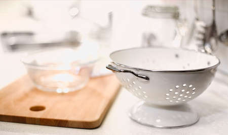 White modern utensils of colander and glassware composed with wooden cutting board on white counter of light kitchen