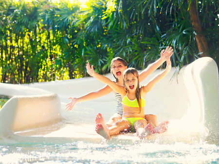 Cute little girsl on water slide at a vacation resort with background of tropical plants