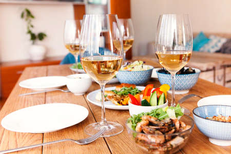 High angle of wooden table served with various homemade dishes and glasses with wine in cozy living room at home