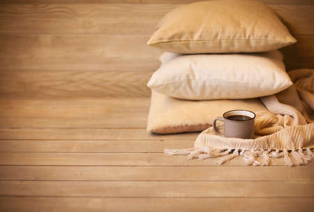 Pillows and cup of beverage against blurred wooden wall as symbol of warmth and comfort at home
