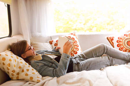 Side view of positive teen girl in casual clothes and glasses lying on bed near window and reading book while resting inside camper 版權商用圖片