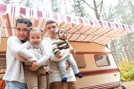 Portrait of a young smiling family while hugging near house on wheels outdoors