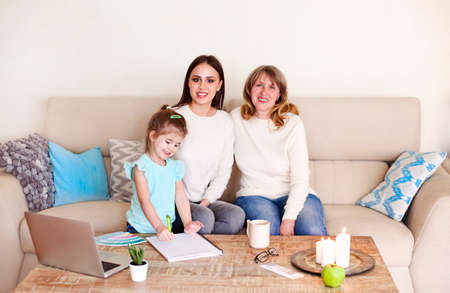 Happy young woman with charming girl and middle aged mother sitting together on couch at home