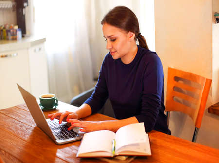 ユーグ女性フリーランサーは、本と木製のテーブルで自宅からリモートで作業しながら、ラップトップ上で入力します