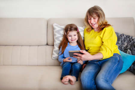 Cheerful little girl and her grandmother sitting on cozy couch and watching photos on mobile phone 版權商用圖片