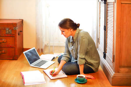 Young female freelancer sitting on floor near cup of coffee and open planner and browsing laptop while working on design project at home