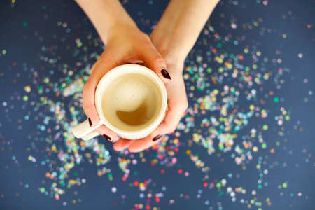 Top view of  female holding mug of warming coffee above navy blue background in glowing confetti