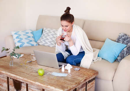 Ill female with cup of hot tea while sitting on couch near table at home