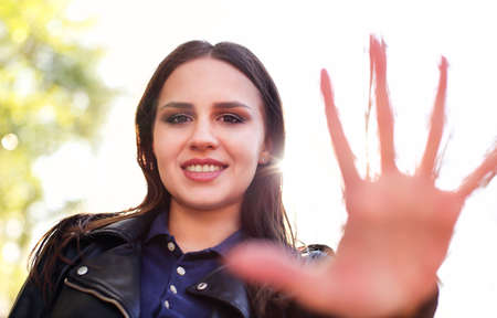 Content young female in leather jacket showing palm at camera and smiling against bright sunlight in park