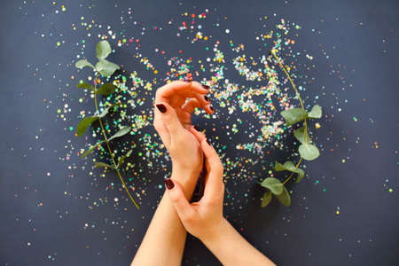 Top view of crop anonymous female holding hands with stylish dark manicure over table with fresh plants and colorful confetti 版權商用圖片