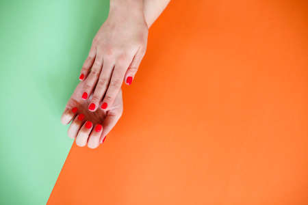 Top view of crop anonymous female with painted dark nails keeping hands over orange and green bright background