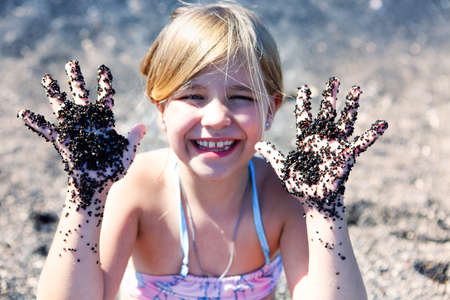 Little cute girl holding hrer hands up with black volcanic sand on them. Summer vacation. Santorini, Greece