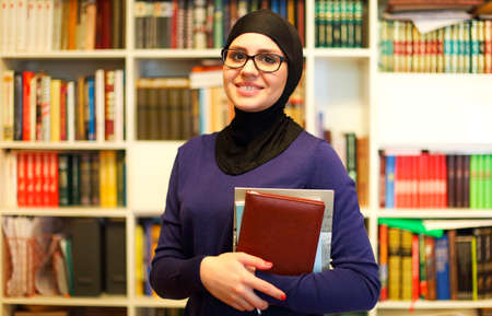 Cheerful woman in headscarf and glasses holding pile of books and smiling at camera standing in library of university 版權商用圖片