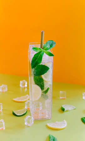 Tall glass of cold mojito drink with citruses and mint leaves placed on green table against orange background