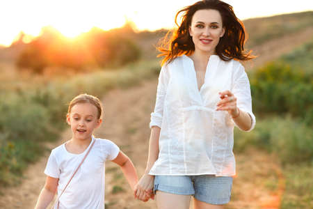 Younng woman and little girl holding hands and walking along sandy road at sunset during weekend
