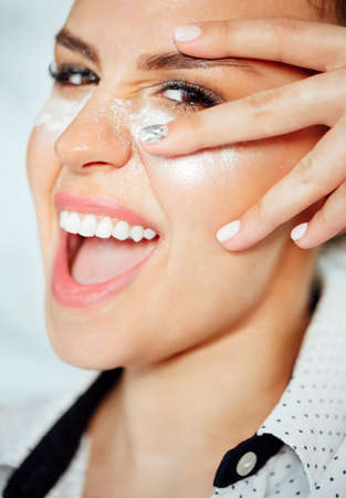 Cheerful young female with white powder under closed eyes smiling and touching cheek during skin care routine