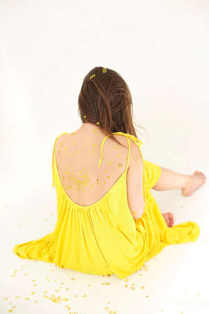 Back view of unrecognizable young female in yellow dress and with confetti skin sitting and having fun against white background Stock fotó