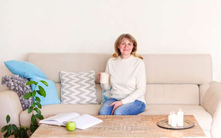 Content relaxed middle aged female enjoying cup of hot tea and smiling at camera resting on couch in living room