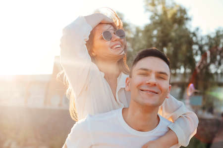 Smiling boyfriend piggybacking delighted girlfriend while enjoying weekend together in summer during sundown