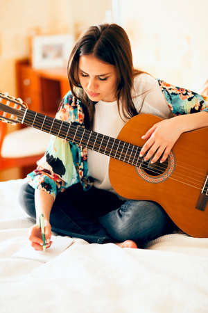 Crop female musician with acoustic guitar and laptop making notes while sitting on bed and writing song at home