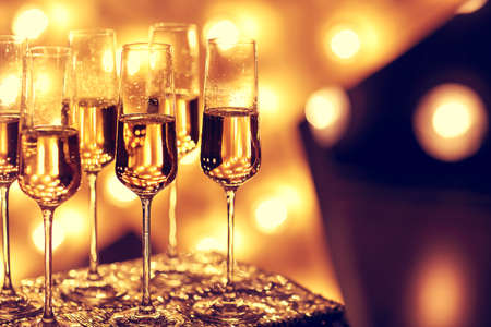 Transparent wineglasses with champagne placed on blurred background of bright illumination during party