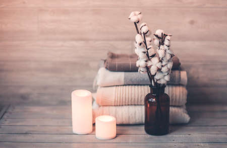 Burning white candles in composition with bouquet of ripe fluffy cotton in transparent brown bottle on rustic wooden table beside finished products like cotton clothes plaid and towel