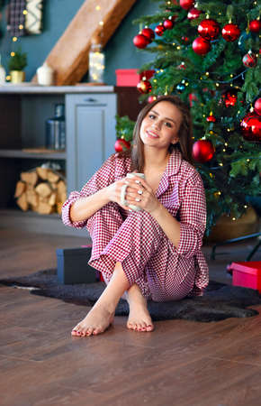 Happy young woman in plaid pajama holding jar smiling at camera in kitchen decorated for Christmas