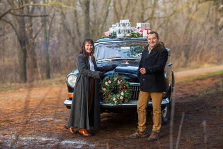Cheerful young couple dressed in warm clothes with sparklers in hands looking at camera while standing by the retro car with presents on the roof Reklamní fotografie