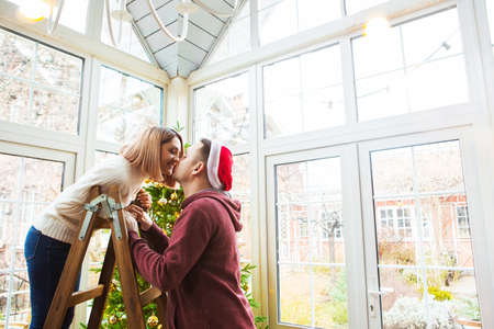 Side view of young woman on stepladder kissing man in Christmas hat during decorating Christmas tree at home Reklamní fotografie