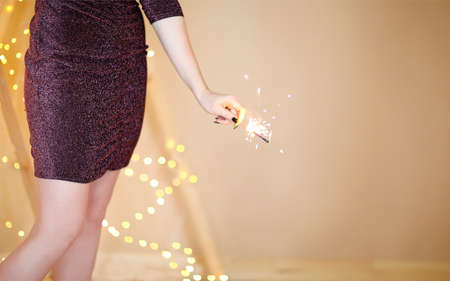 Soft focus of cheerful young female with lit sparkler and glass of champagne standing against shiny illuminated Christmas tree