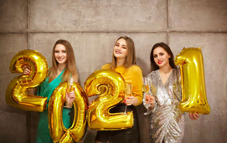 Glamorous young females holding shiny golden balloon numbers 2021 smiling at camera on gray wall