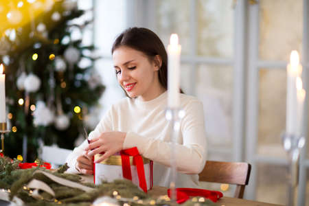 Young girl in white sweater packing round present box tied with bright red ribbon during holiday celebration