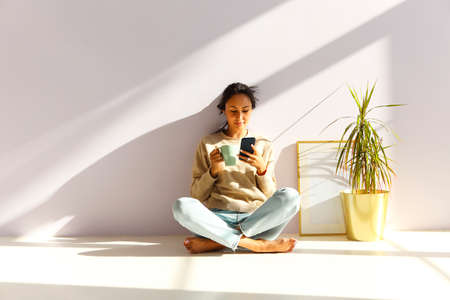 Full body of relaxed young Asian female drinking coffee and browsing social networks on mobile phone while sitting on floor and chilling in light room Stock Photo