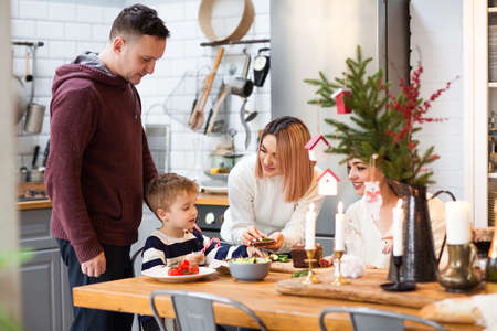 Family with little boy at table having meal enjoying Christmas holiday together