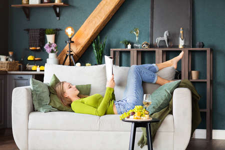 Side view of young female reading interesting magazine while lying on comfortable couch near table with fruits and wine on weekend day at home Foto de archivo