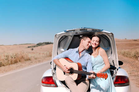 Happy young couple playing guitar and enjoying time together while sitting on open trunk of car parked on country road during summer trip
