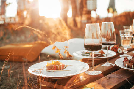 Set of elegant glassware placed on plank wooden table with floral arrangement on grassy meadow during festive autumn picnic