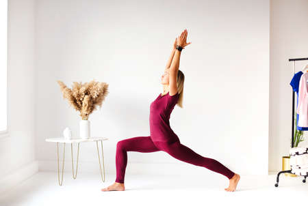Young female in yoga pose and meditating in white room