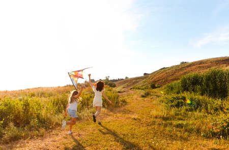 Carefree woman and teenage girl running along field and playing with kite during summer weekend